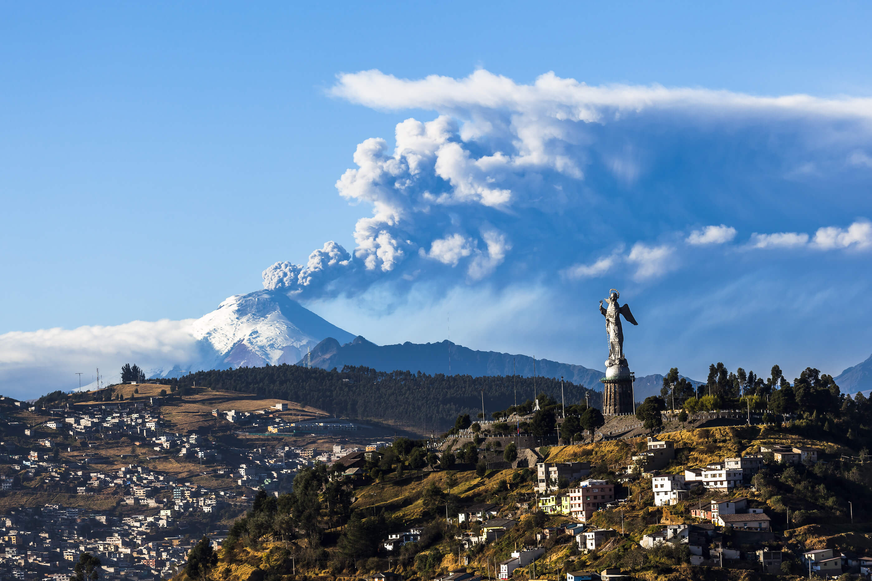Cotopaxi volcano eruption and Panecillo's Madona seen from Quito Ecuador