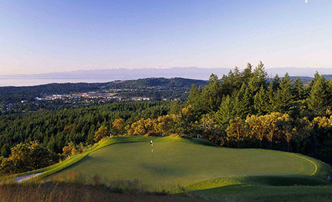 Golf course with green forest and mountains. BC, Canada.