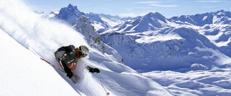 Skiing down a steep slope with lots of powder. Arlberg, Austria.
