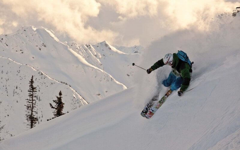 Skiier making a sharp turn on the hill. Kicking Horse, BC.