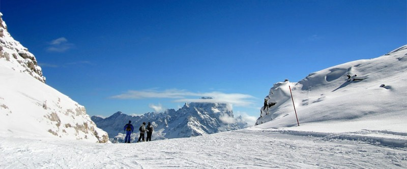 Skiiers enjoying the view on the top of their trail. Cortina, Italy.