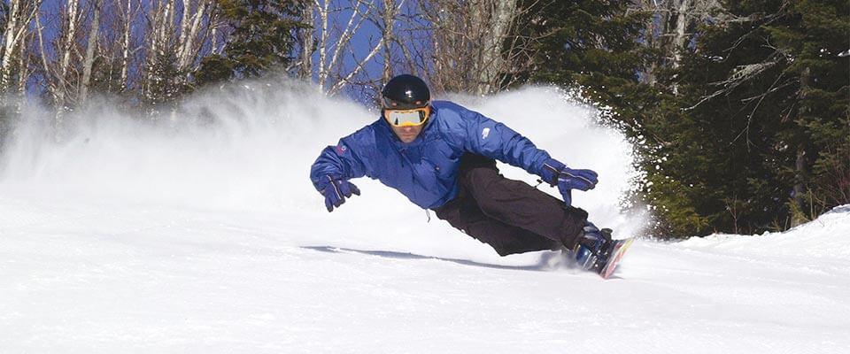 Snowboarder carving. Le Massif, Quebec.