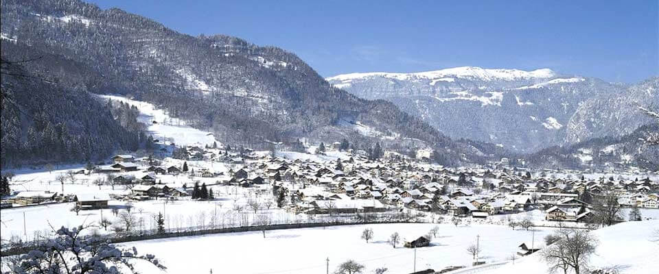 Ski village view from afar with snowy mountains. Grindelwald, Switzerland.