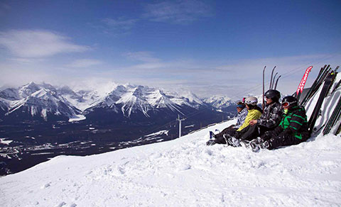 Skiiers taking a rest on the hill top in the snow. Alberta.